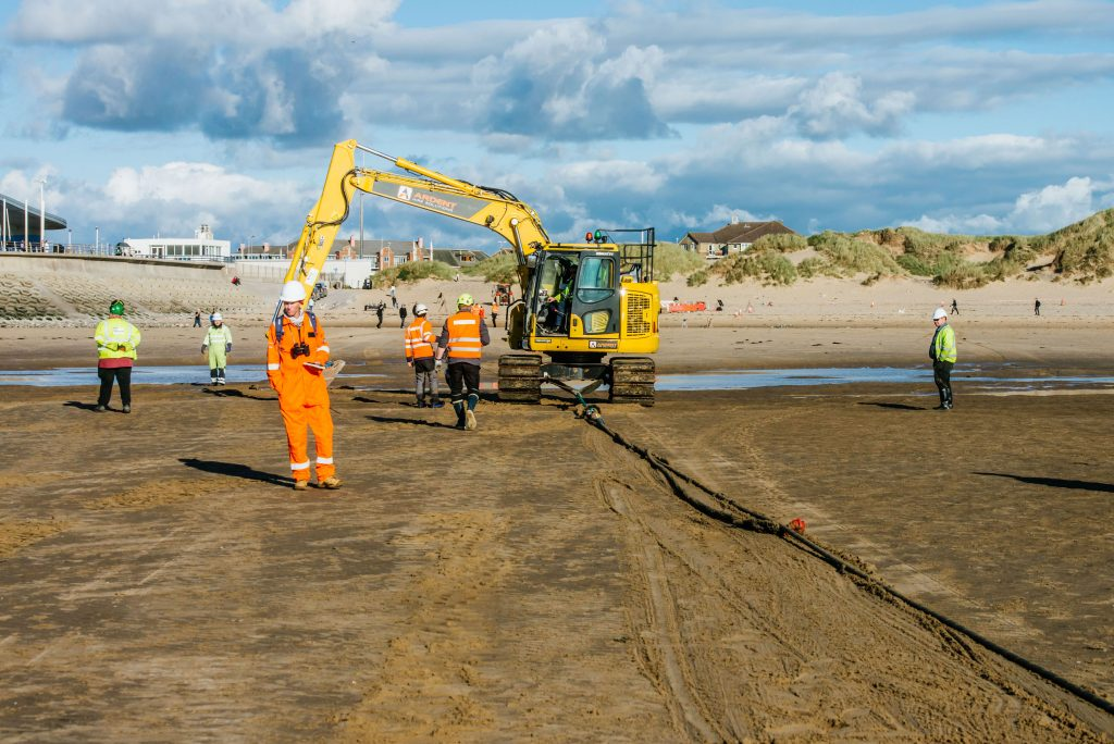 diggers drag the cable up the beach to the existing ducting system that links to the landing station at Blackpool Airport Enterprise Zone.