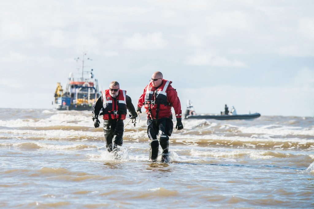 Divers coming ashore after connecting the cable to flotation device